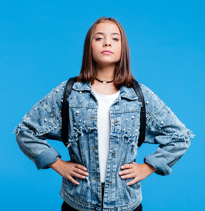 Confident female high school student wearing oversized denim jacket and white t-shirt, standing against blue background. Portrait of power girl.