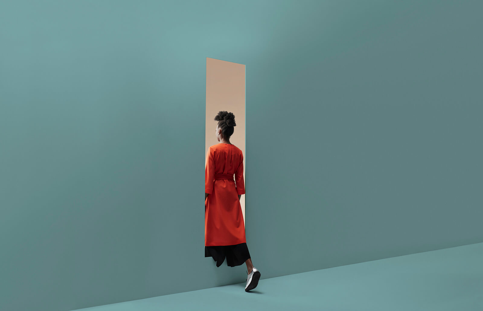 A woman in a red dress is crossing a doorway into another room. Each room is blank, with one room colored blue and the other a golden hue.