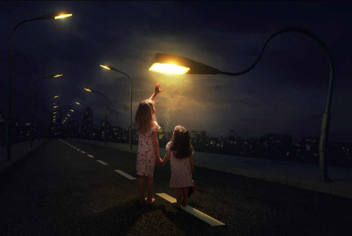 Two young girls are holding hands and walking down a street with many streetlights on its sides. A streetlight bends down to one of the girl's arms, which is outstretched as if trying to touch the light.