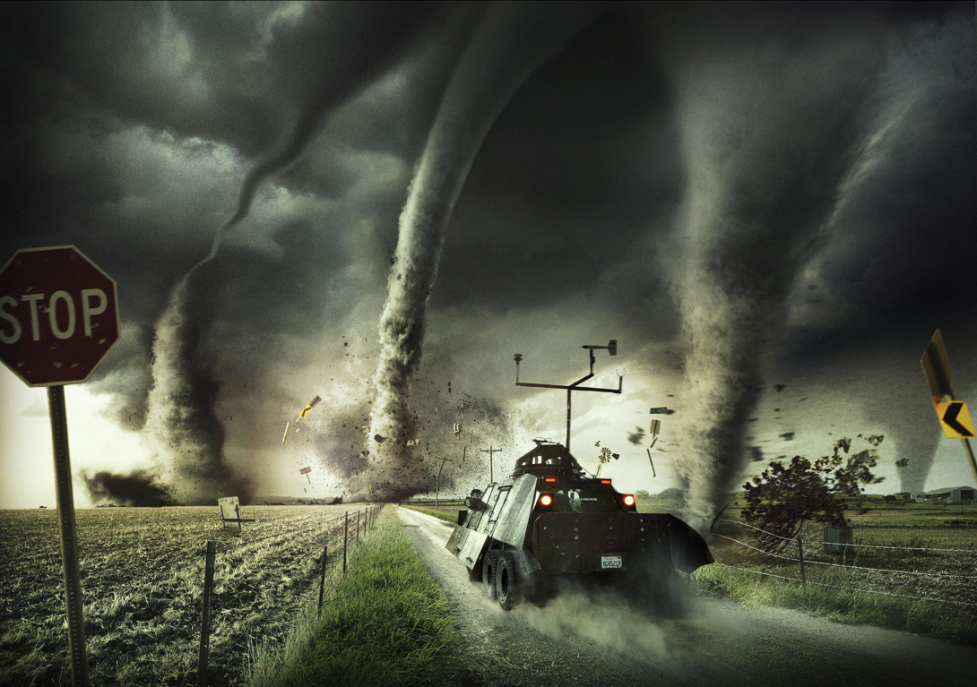 A military-style vehicle is speeding down a dirt road with four tornadoes in its path. Fields can be seen on either side of the road.