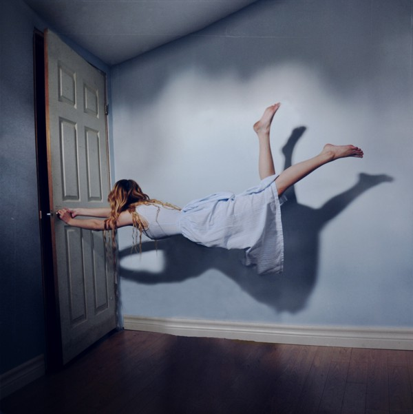 A young woman is suspended in an empty room. There are wood floors and painted walls, which look like a bedroom, and the woman is grabbing the doorknob to her room to keep from floating higher. It looks as if there is no gravity.