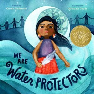 We are water Protectors book cover. Features a Sioux girl in purple and read, holding a feather. She is surrouned by water and the crescent moon is behind her.