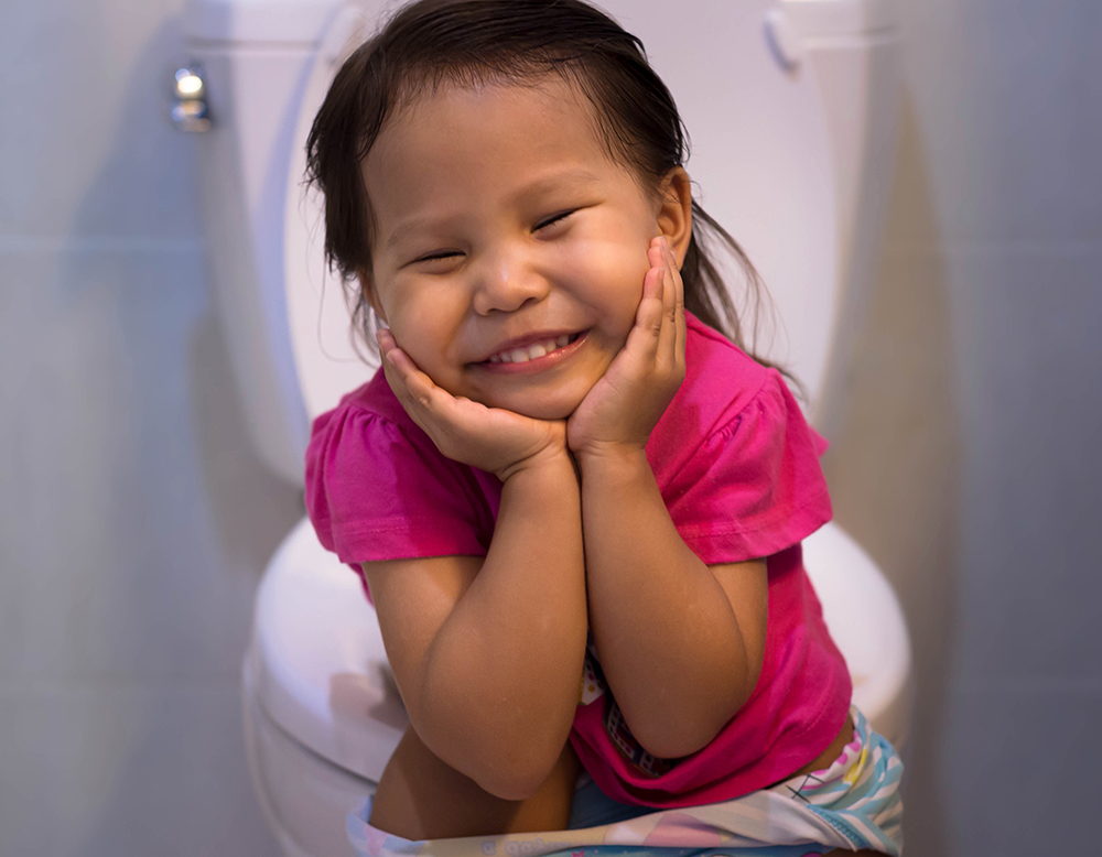 Happy little girl proud of sitting on the toilet at home.