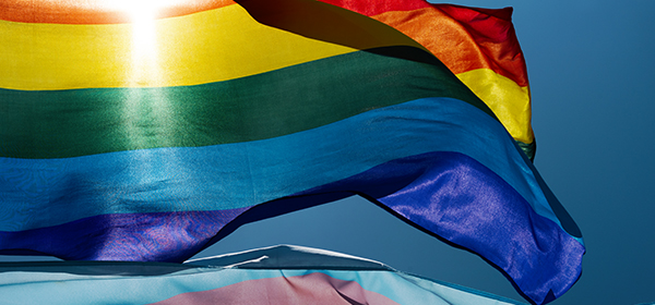 closeup of a gay pride flag and a transgender pride flag