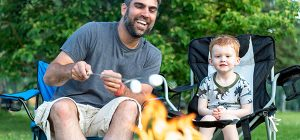 Father and Son Roasting Marshmallow over Campfire in Camping in Summer