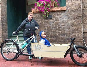 mom taking kid around town in a cargo bike