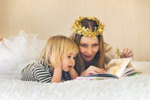 Mother and cute little child reading in bed. Having fun in imaginary land.