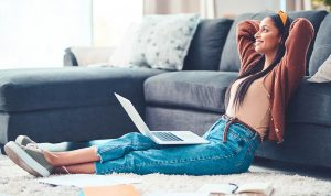 young woman relaxing while working in the living room at home