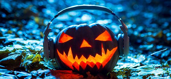 Jack-o-Lantern with headphones at night on leaves